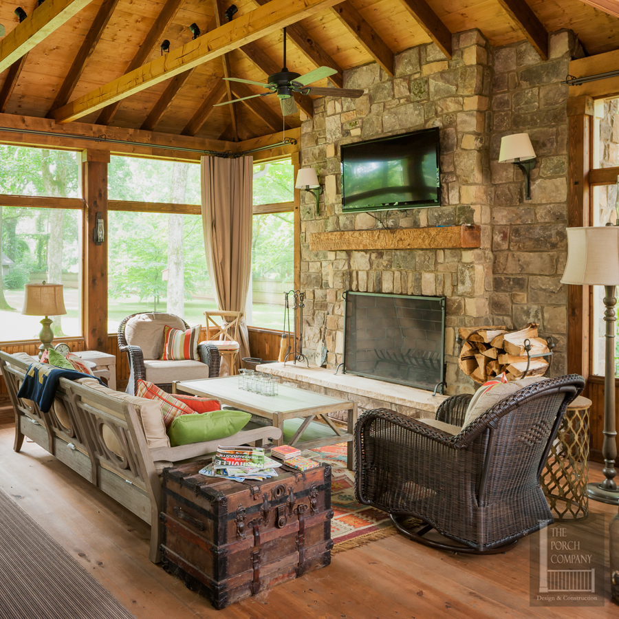 Screened Porch With Exposed Rafter Ceilings And Fireplace