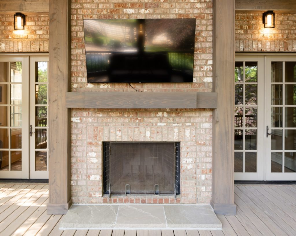 Classic brick porch fireplace with stone hearth and custom mantel by The Porch Company